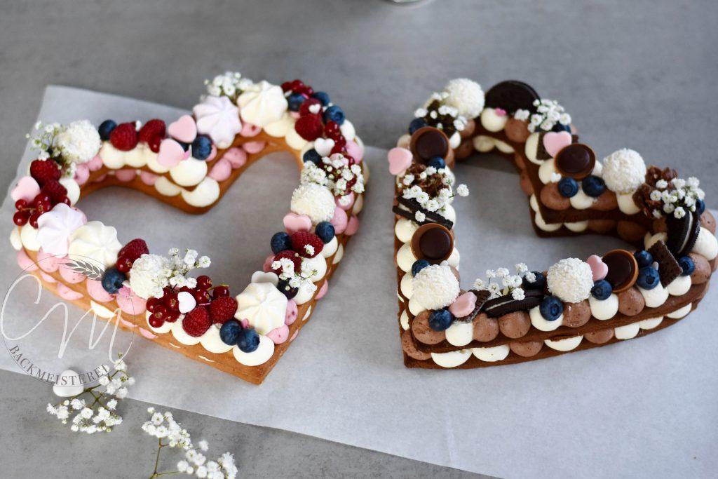 Zwei Herzkuchen in Herzform. Dekoriert mit Beeren, Süßigkeiten und Blumen.